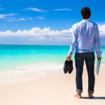 Young man with laptop on the background of turquoise ocean on tropical beach